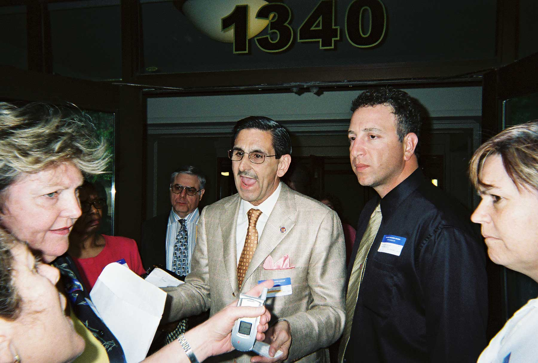 "June 1, 2005. Chicago Teachers Union Vice President Ted Dallas (above, center) talks with irate union members including School Clerk Delegates Maureen Callaghan (left) and Schurz High School Delegate Lois Jones (right) after someone from the CTU leadership tried to have former CTU President Deborah Lynch arrested. The verbal and sometimes physical attacks on Lynch during Marilyn Stewart's first term (2004-2007) have long been compared to the dirty tricks conjured up for the Bush Administration in Washington, D.C., by Karl Rove. Of all the dirty tricks, the nastiest came with the arrest of Lynch, who was escorted out of the House meeting by two armed Chicago police officers. At the time, several observers believed that Dallas had called the police, and the police told Substance reporter George Schmidt that the call came from someone identifying himself as the ""vice president."" Dallas claimed that he had not called the police. Lynch was released from police custody after CTU officials refused to sign the arrest complaint that she had been ""disorderly"" during the House of Delegates meeting. Others in the photograph above are CTU security coordinator Rick Perrote (behind Dallas), who is now an officer of the Marilyn Stewart faction of the ""UPC,"" and Ted Hajiharis (a field rep, to the right of Dallas). Two complete stories about the incident (""Scofflaw Union Chiefs Run Outlaw Meeting"" by Theresa Daniels and ""CTU officials attempt to arrest Deborah Lynch"" by George N. Schmidt are still available on the ""old"" Substance Website at www.substancnews.com. The new Substance site is www.substancenews.net. Substance photo above from the June 1, 2005 CTU meeting by George N. Schmidt."