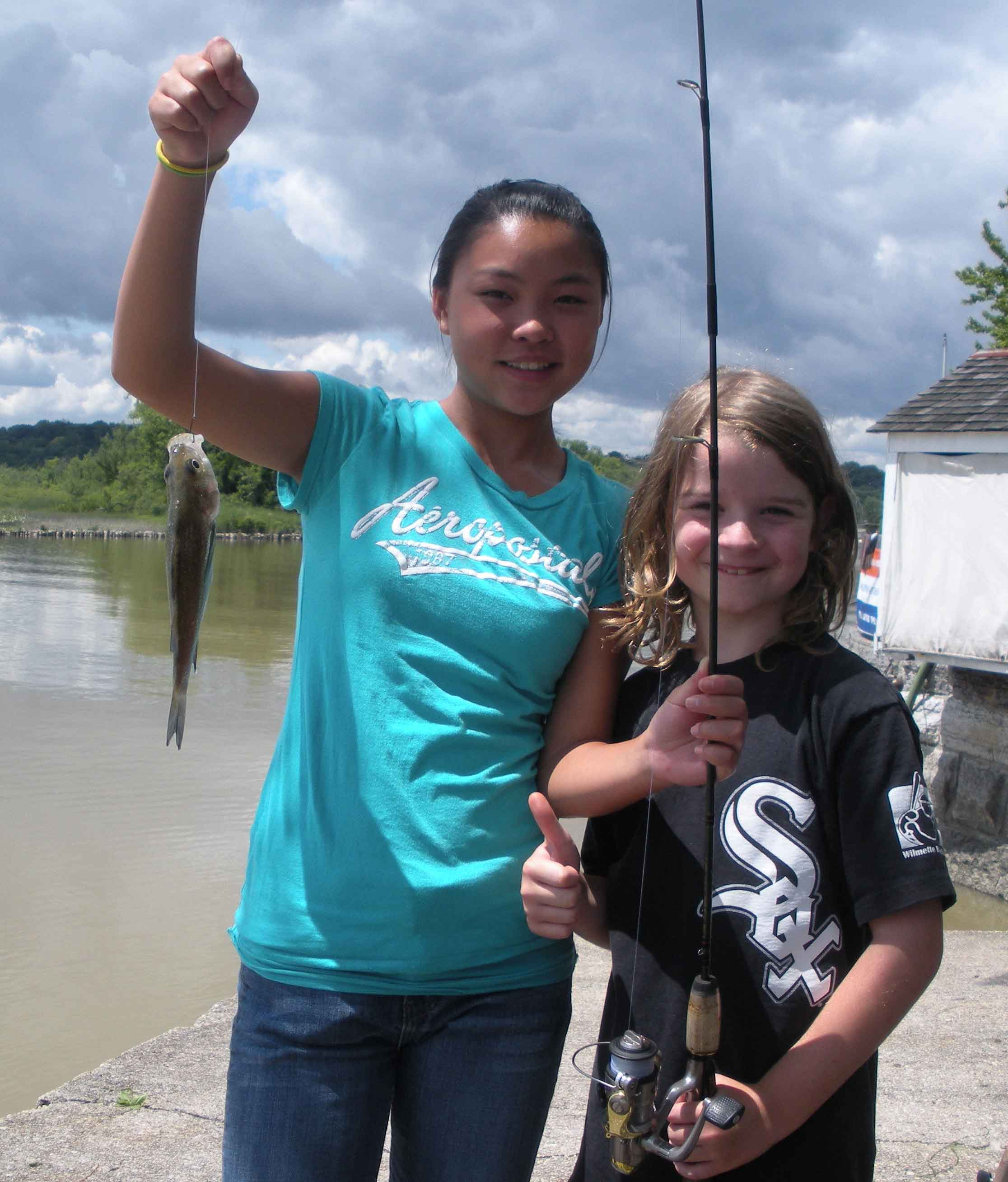 White Sox fan Sam Schmidt (above right) stands as his cousin Jade Forman displays the first fish Sam ever caught on July 10, 2009, at the Hudson River lighthouse in Saugerties, New York. Sam Schmidt, Substance elementary education editor and nature photographer, joined the early boycott of standardized testing in the USA on May 11 and May 12, 2010, by sitting out the tests at his public school in Chicago, while American teachers decide whether to join with their British brothers and sisters in ending the noisome reign of so-called standardized tests in the USA. Substance photo by George N. Schmidt.