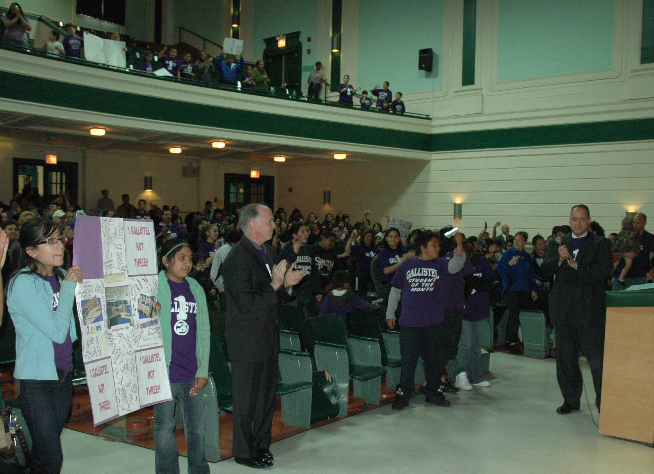 "Holding a sign and wearing purple tee shirts that read ""One Gallistel, Not Three"", more than 600 students, teachers, parents, and community supporters nearly filled the auditorium at Morgan Park High School on May 22, 2008. The Gallistel Elementary School contingent arrived by car and in 13 buses, making them the largest contingent to testify during the six-day hearings on the Board of Education's Capital Development program in May. Standing at the podium on the right (above) and wearing his Gallistel tee shirt is Alderman John Pope (10th Ward) who spoke about the need for a new Gallistel school to consolidate the present three-school reality. Gallistel supporters filled most of the main floor of the large auditorium and the front row of the balcony. Whether Gallistel ever gets relief from its problems is another question, one not answered by the officials who hosted the hearings. Since Arne Duncan became CEO of the Chicago Public Schools in July 2001, schools like Gallistel, which proudly proclaim that they are public schools, have been short changed in all capital expenses, while school improvement and construction budgets are manipulated to support privatization schemes and other programs promoted by Chicago Mayor Richard M. Daley. Substance photo by George N, Schmidt."