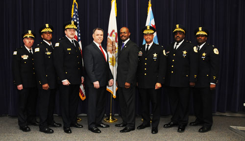 The only person with less than 20 years Chicago police experience in the above photo is the man center left in the red tie: Police Supt. Garry McCarthy. The other seven officers whose promotions were announced on April 18, 2013 were all from inside the department, with vast experience from the streets to the supervisory offices. City of Chicago photo provided by Chicago Police Department.