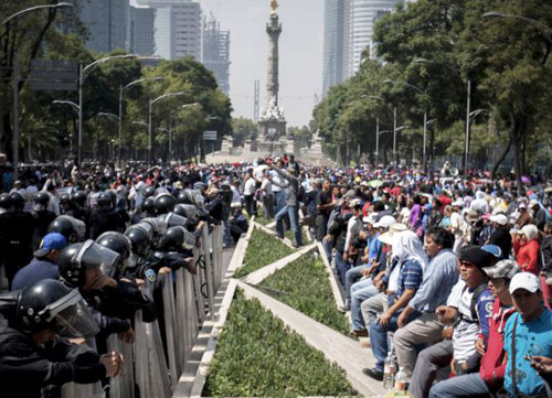 Mexican teachers (right) were standing up against corporate