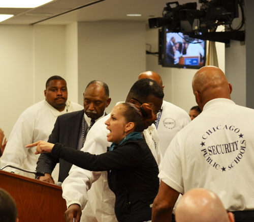 Parent activist Rousemary Vega (above, pointing) was swarmed by five security people at the May 28, 2014 meeting of the Chicago Board of Education. Substance photo by George N. Schmidt.